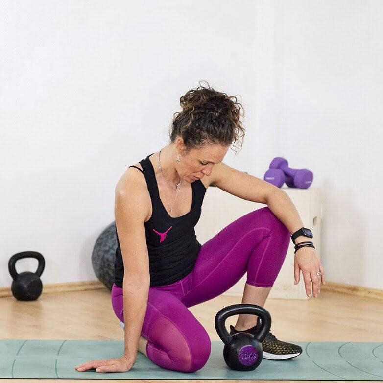 vrouw met kettlebell op sportmat